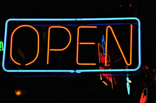 A neon sign outside a pub in the evening