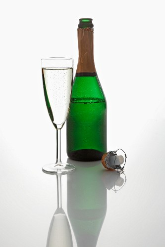 A bottle and a glass of sparking wine, and a champagne cork