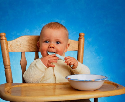 A baby sitting in a high chair with a wooden spoon in its mouth