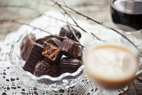 A bowl of filled chocolates with a glass of Baileys and one of Kahlua