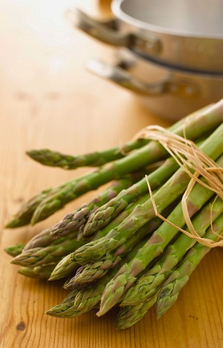 A bundle of asparagus with cooking equipment in the background
