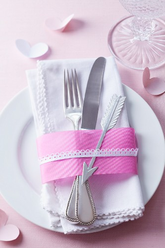 Cutlery on napkin decorated with ribbons & silver Cupid's arrow