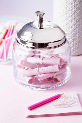 Glass container with rolled pieces of paper for wedding messages