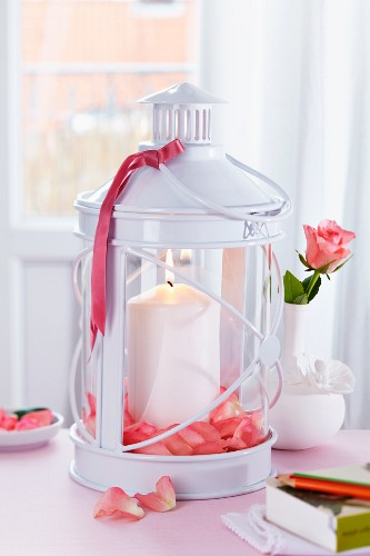 Candle in lantern decorated with rose petals