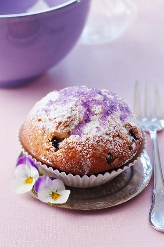 Muffin mit Puderzucker und lila Veilchenzucker
