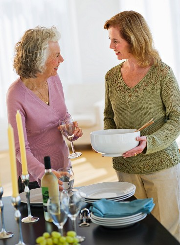 USA, New Jersey, Jersey City, Mother and daughter setting table in home