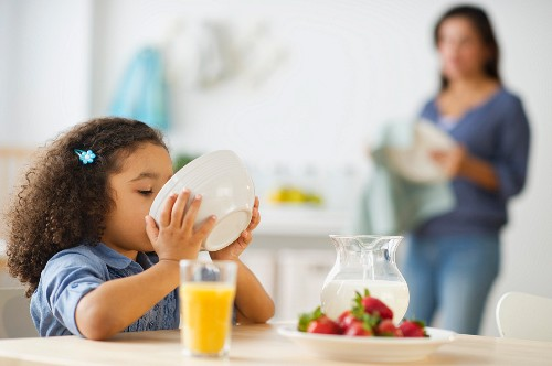 USA, New Jersey, Jersey City, girl (6-7) eating breakfast with defocused mother in background