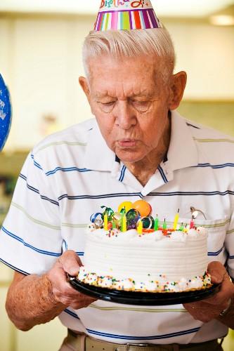 Senior man blowing candles on birthday cake
