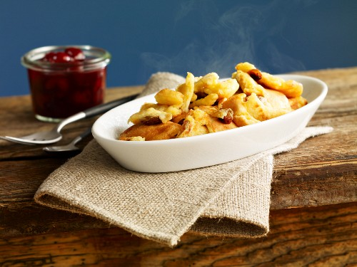 Kaiserschmarren (sweet cut up pancakes) in a casserole dish with cherry compote
