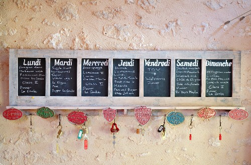 A blackboard divided into days of the week, with small metal signs attached to the chalk tray