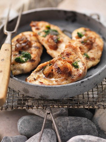 Marinated barbecued pork steaks in a dish on the barbecue
