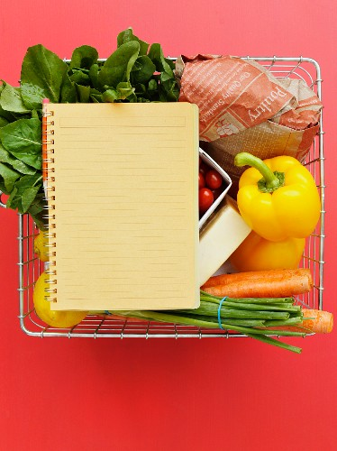 A shopping basket with vegetables, lemons and a notebook