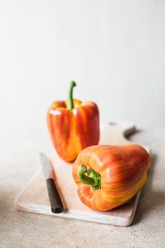 Fresh striped red peppers on a chopping board with a knife