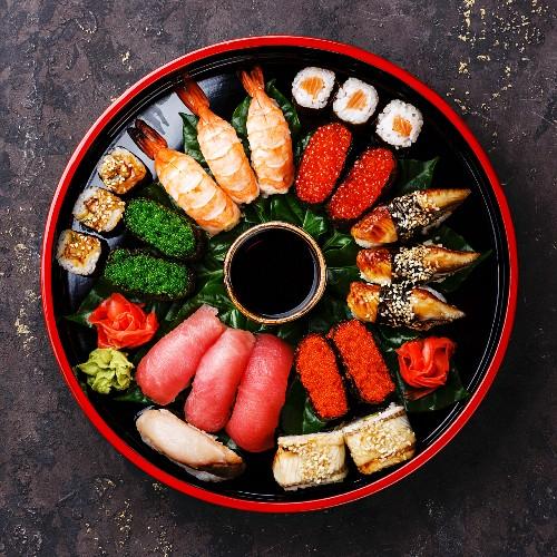 Sushi Set nigiri, rolls, gunkan and sashimi served in traditional Japan black Sushioke round plate