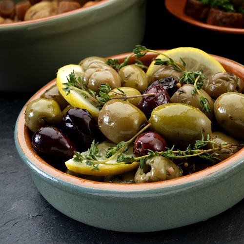 Marinated olives with thyme and lemon served as tapas in a dish