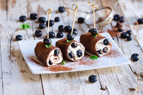 Chocolate pancake rolls with cream cheese and blueberries