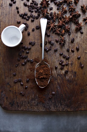 An arrangement of coffee beans, coffee powder and star anise