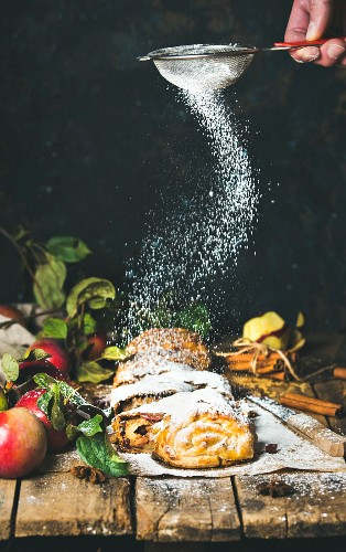 Hand with sieve sprinkling sugar powder on apple strudel cake with cinnamon and fresh apples