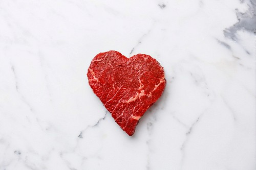 A heart-shaped cut of fresh beef on a marble surface