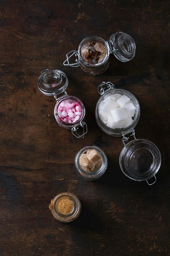 Different glass jars with variety of sugar white, brown pink fruit granulated, cubes and crystal