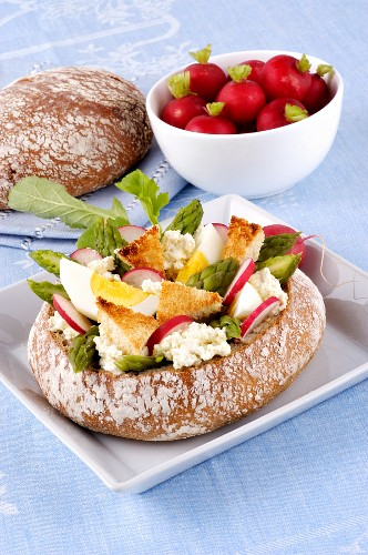 A load of bread filled with goats' cheese, egg, asparagus and radish