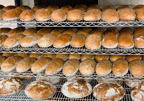 Loaves of white bread sprinkled with poppy seeds on shelves in a bakery