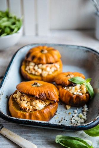 Pumpkins stuffed with couscous and feta, garnished with basil