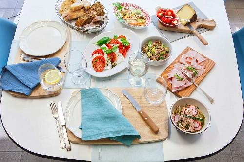 A set table for evening tea with salads, bread, cold cuts and cheese