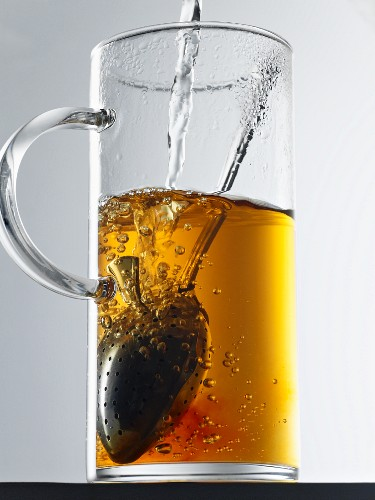 Assam tea in a glass with a tea infuser