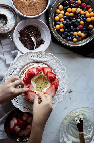 A vanilla cake being decorated with fresh strawberries
