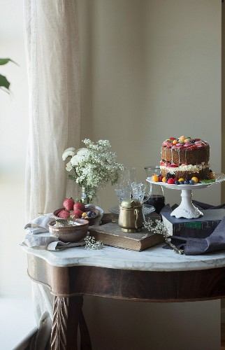A vanilla cake decorated with fresh fruit on a cake stand