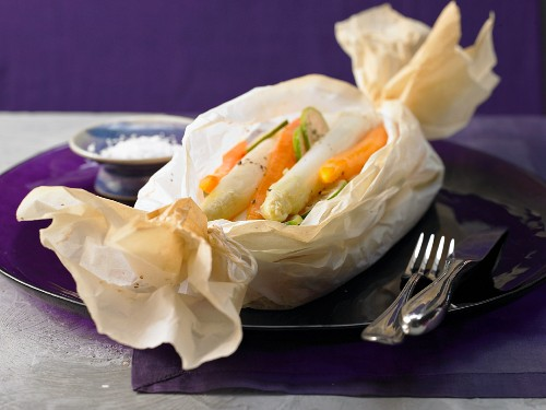 White asparagus wrapped in paper with carrots and ginger