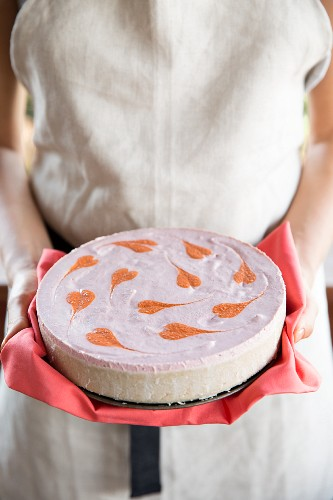 A woman holding a vegan cheesecake with strawberries and goji berries