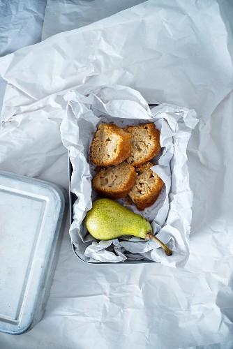 Brotdose mit Birne und vier Stücken veganem Birnengugelhupf aus Dinkel- und Maismehl, gesüßt mit Kokosblütenzucker