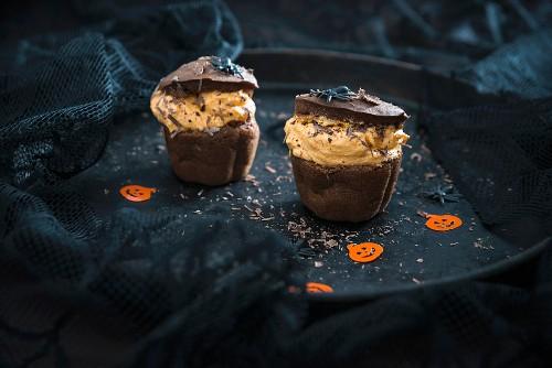 Vegan chocolate and pumpkin cupcakes with orange cream filling for Halloween