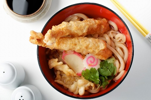 A broth with wheat noodles, vegetables and prawn tempura (Asia)
