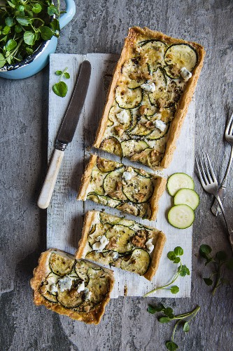 Savoury blue cheese and courgette tart topped with walnuts, sliced