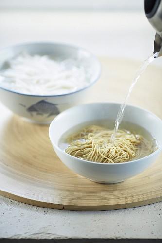 Asiatische Nudeln mit Wasser aufgiessen