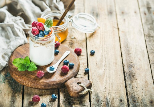 A glass jar of white yoghurt with fresh berries, peach and mint on a wooden serving board