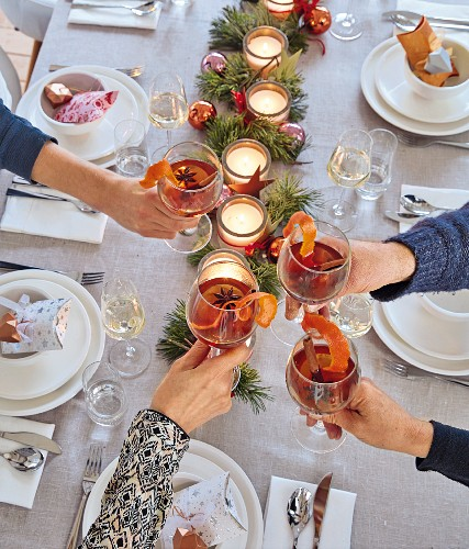 Hands raising glasses of mulled wine over a festively set dining table