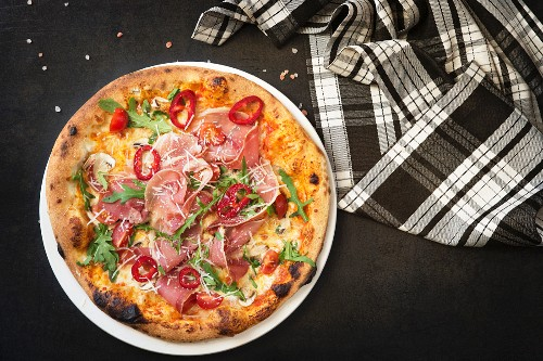 Pizza with ham, cheese and rocket