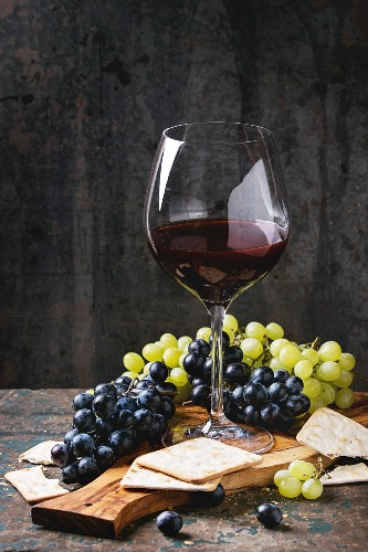 Bunches of ripe wet red and white grapes with crackers snack and glass of red wine on olive wood cutting board