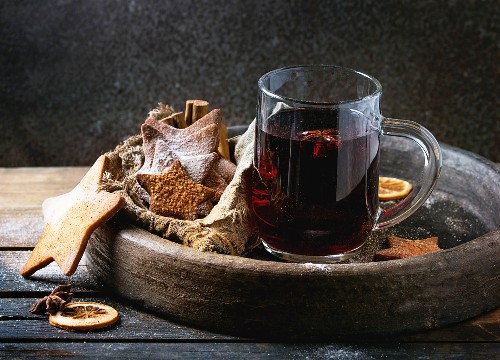 Glass mug of hot red mulled wine spices, sugar shortbread cookies star shape, anise and cinnamon powder in clay tray