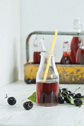 Cherry juice in a glass bottle with a straw, bottles in a bottle carrier and fresh cherries