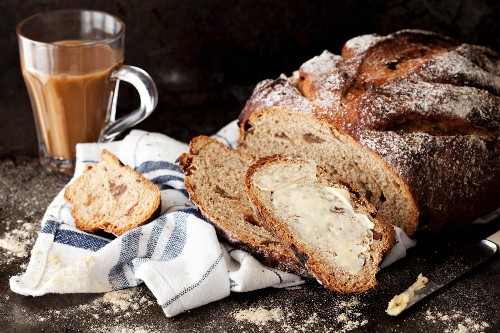 Rice bread with dates, spread with butter, and coffee in a glass