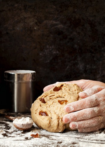 Hands shape rice bread dough with dates into a loaf