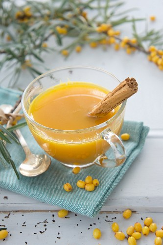 Hot orange juice with seaberries and a cinnamon stick
