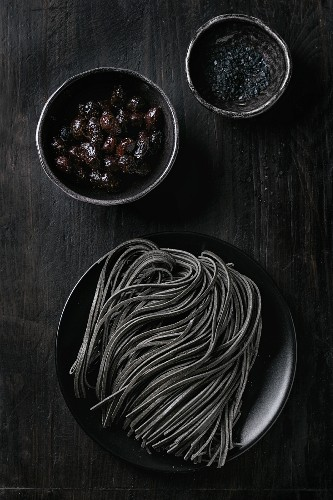 Raw uncooked black cuttlefish ink spaghetti pasta with black olives and black salt over black background View from above