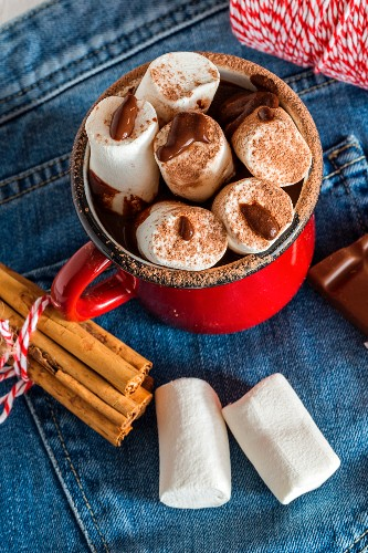 Mug with hot chocolate with marshmallow on old wooden board