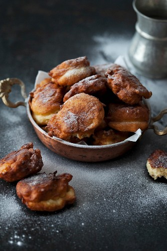 Apple dough fritters with powdered sugar on a dark background